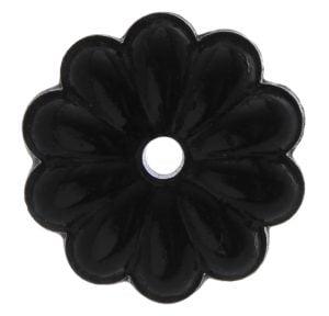 Musta, kukan muotoinen kristalli, jossa on keskellä reikä.