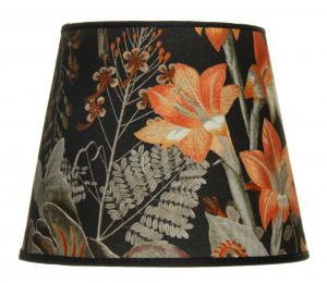 Valkoisella taustalla valokuva lampunvarjostin, joka levenee suorassa linjassa ylhäältä alaspäin. Varjostimen ylä- ja alareunat ovat kaarella. Varjostimen pohjaväri on musta, ja sitä koristaa runsas sekä värikäs kukkakuviointi. Kuvioinnin kukat ovat oransseja, Kuvioinnin oksat sekä lehdet ovat vihreitä. Varjostimen ylä- ja alalaidassa on mustat kanttausnauhat. Varjostin on kuvattu edestä.