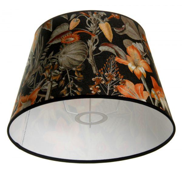 Valkoisella taustalla valokuva lampunvarjostin, joka levenee suorassa linjassa ylhäältä alaspäin. Varjostimen ylä- ja alareunat ovat kaarella. Varjostimen pohjaväri on musta, ja sitä koristaa runsas sekä värikäs kukkakuviointi. Kuvioinnin kukat ovat oransseja, Kuvioinnin oksat sekä lehdet ovat vihreitä. Varjostimen ylä- ja alalaidassa on mustat kanttausnauhat. Varjostin on kuvattu alaviistosta, jolloin sen valkoinen sisäpinta sekä osa valkoisesta kiinnitystelineestä ovat näkyvissä.