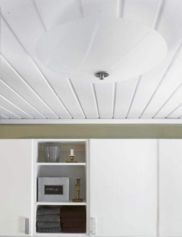 """Valkoisessa lautakatossa etsattu, pyöreä plafondi, jossa on valkoisia viivakuvioita. Huoneen seinä on oliivinvihreä. Kuvan alaosassa on kaapit, joissa on valkoiset ovet ja yksi avohyllykkö, jossa ylimpänä on harmaa kukkaruukku ja antikmessinkinen kynttiläjalka valkoisella kynttilällä, alempana metallinen laatikko, jossa lukee """"LAMPPUJA"""" sekä kaksi antikmessinkistä kynttiläjalkaa, ja alimmalla hyllyllä on kahdessa rivissä pyyhkeitä, vasemmmalla harmaita ja oikealla tumman violetteja."""