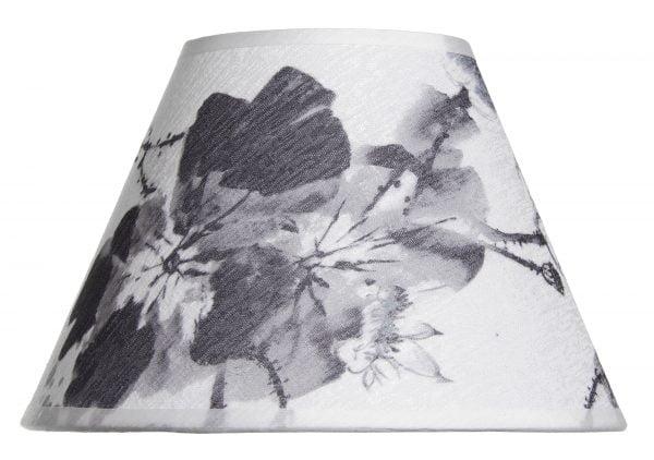 varjostin on pääväriltään Valkoisella taustalla valokuva lampunvarjostin, joka levenee suorassa linjassa ylhäältä alaspäin. Varjostimen ylä- ja alareunat ovat kaarella. Varjostimen pohjaväri on valkoinen, ja siinä on harmaasävyisiä, suuria kukka- sekä lehtikuvioita. Varjostimen ylä- ja alareunassa on hieman läpikuultava, valkoinen kanttausnauha. Varjostin on kuvattu suoraan edestä.