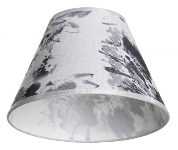 varjostin on pääväriltään Valkoisella taustalla valokuva lampunvarjostin, joka levenee suorassa linjassa ylhäältä alaspäin. Varjostimen ylä- ja alareunat ovat kaarella. Varjostimen pohjaväri on valkoinen, ja siinä on harmaasävyisiä, suuria kukka- sekä lehtikuvioita. Varjostimen ylä- ja alareunassa on hieman läpikuultava, valkoinen kanttausnauha. Varjostin on kuvattu alaviistosta, jolloin sen valkoinen, hieman läpikuultava sisäpinta on näkyvissä.