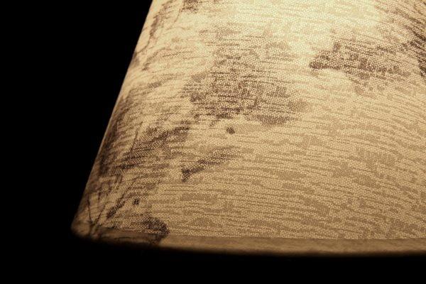 Valokuva lampunvarjostimesta, jonka sisällä palaa valo, joka tuo esille kankaan pinnassa olevan kuvioinnin. Varjostin näkyy kuvassa beigen sävyisenä. Tausta on musta. Valaisimessa on tummaa kuviointia.