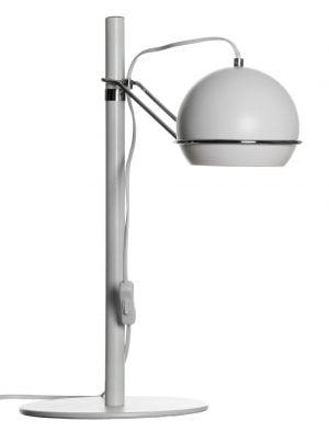 Valkoisella taustalla valokuva valkoisesta pöydävalaisimesta, jossa on valkoinen johto vasemmmassa reunassa, pyöreä pohja, suora runko ja kromatun varren pääss pyöreä varjostin.