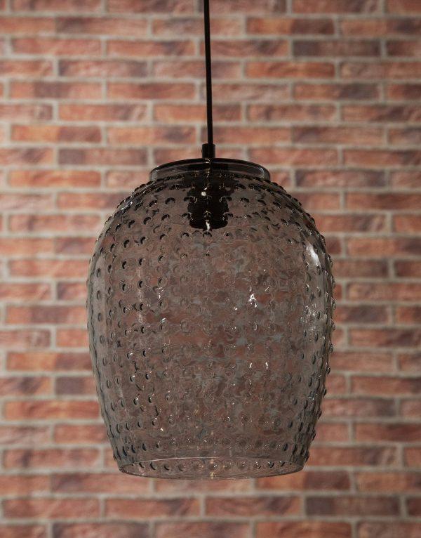 Punaista tiiliseinää vastan valokuvattu harmaa riippuvalaisin, ja sen pinnassa on symmetrisesti nyppykuviointia. Valaisin on valmistettu lasista, ja siitä näkyy läpi. Valaisin on kuvattu alaviistosta.