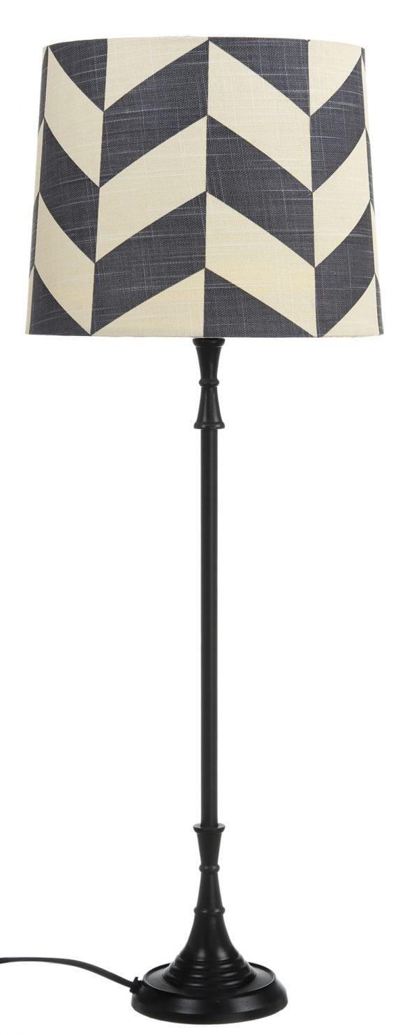 Metallinen musta pöytävalaisin. Pöytälamppu jonka kalanruotokuvioinen varjostin on laminoitua kangasta.