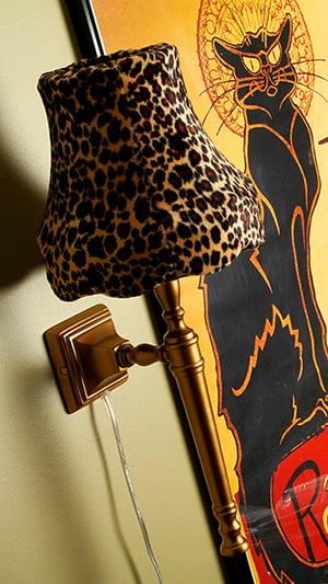 Kultainen seinävalaisin, jossa on leopardikuvioinen samettivarjostin. Huoneen seinä on vihreä, taustalla keltamusta juliste.