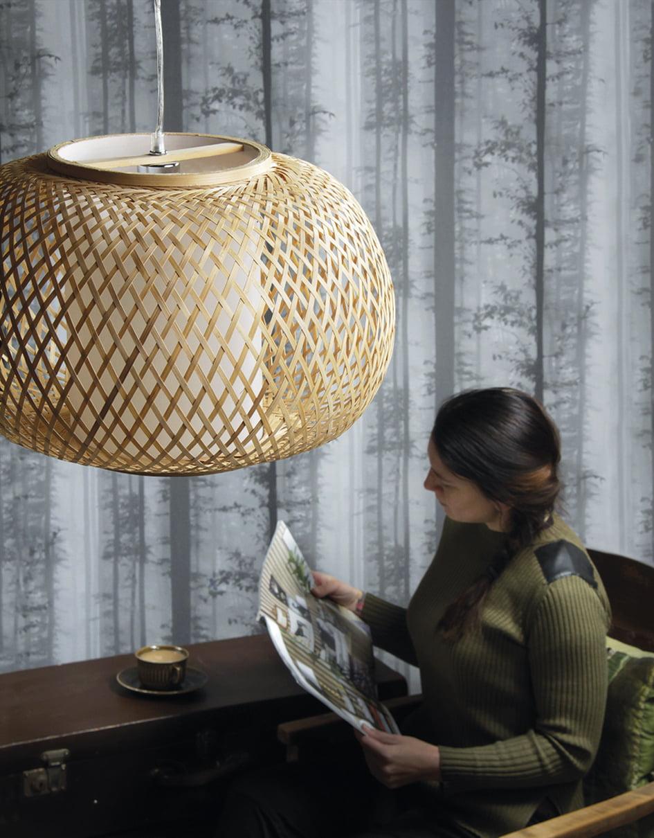 Kuvassa on ripustettava bambuvalaisin, sekä henkilö, joka lukee lehteä. Henkilön vieressä on ruskea pöytä jolla on kahvikuppi.