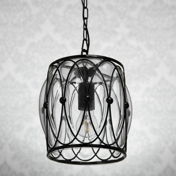 Riippuva, lasinen katto valaisin. Valaisin on kirkas ja sen lasi on metallisen mustan kehikon sisällä.