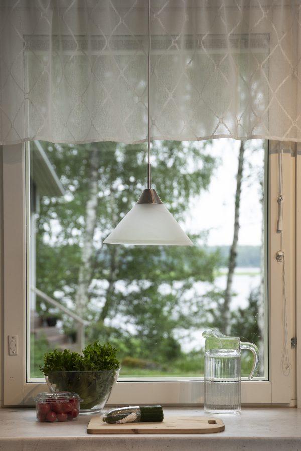 Lasinen, marmorikuvioitu riippuva kattovalaisin ikkunan edessä, työtason yllä.